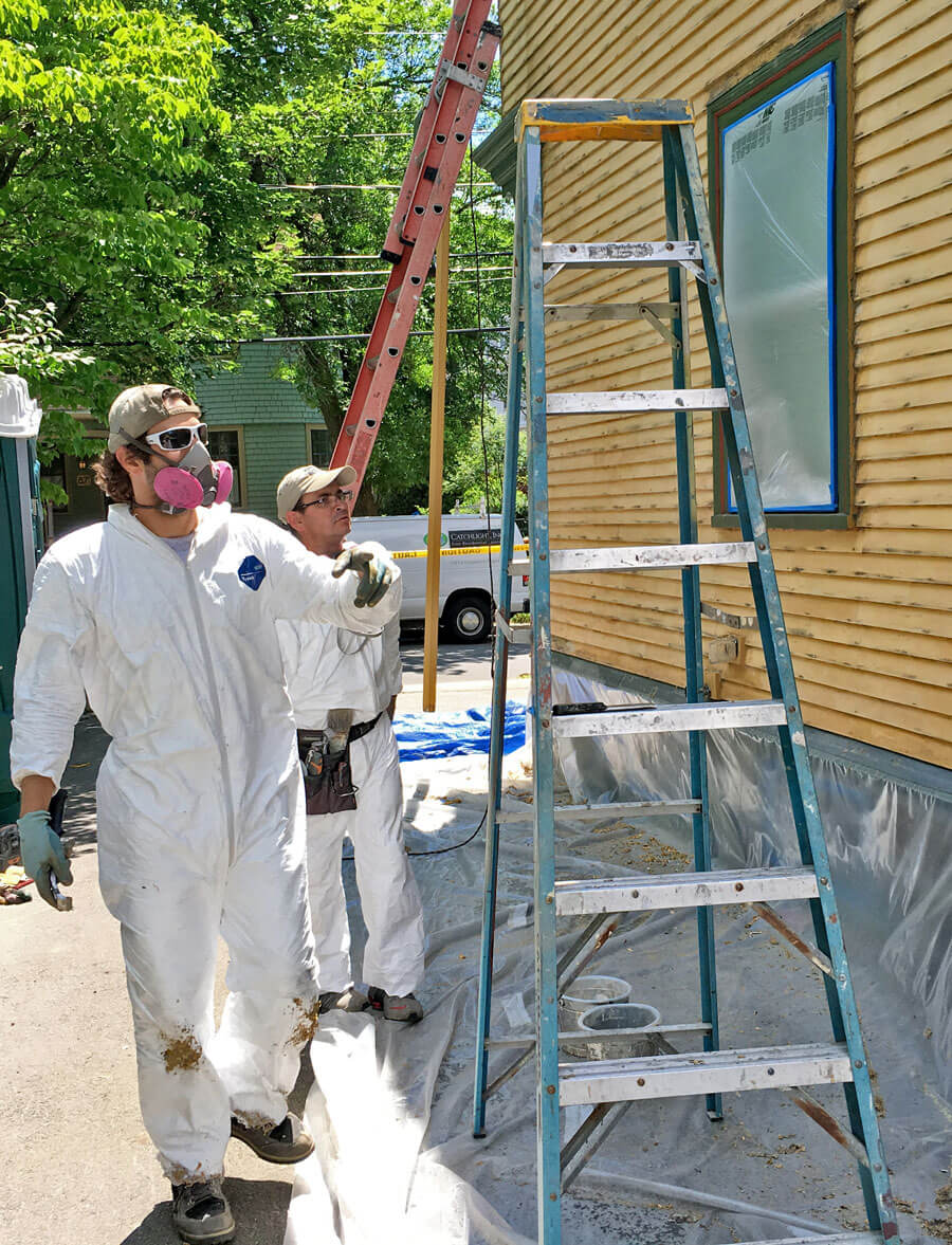 Painters following lead safety precautions while working on the side of a house