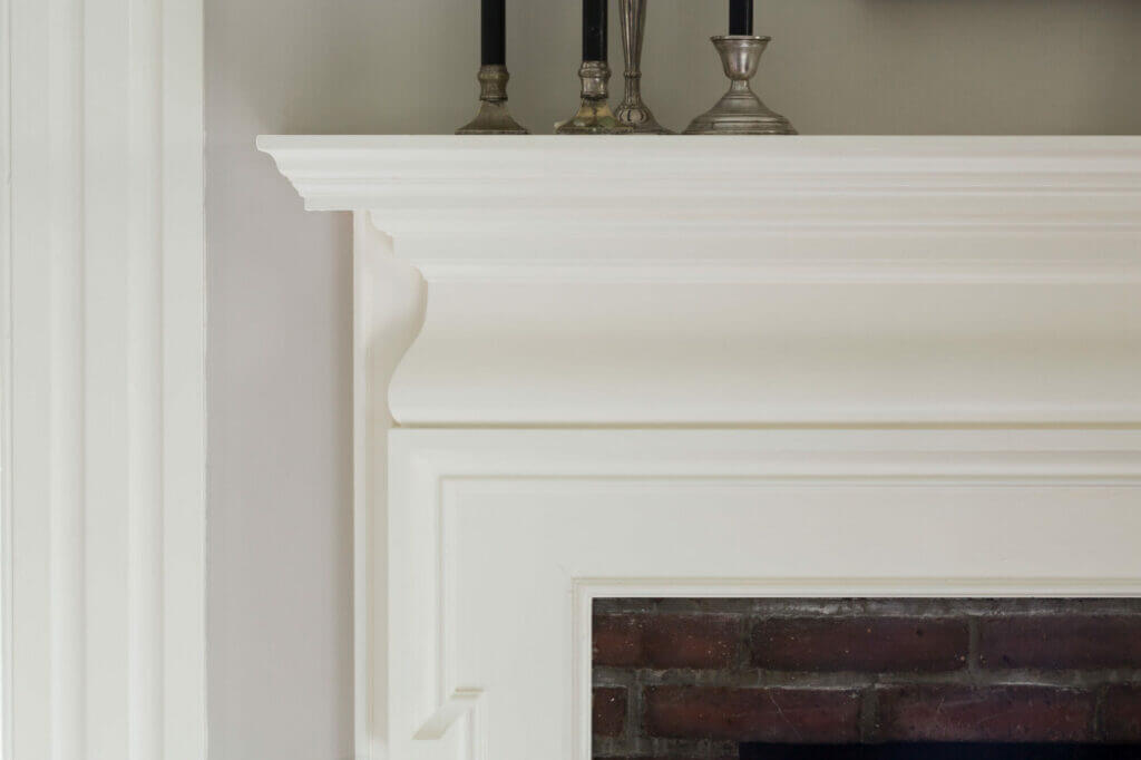 Complementary white trim glosses on a fireplace